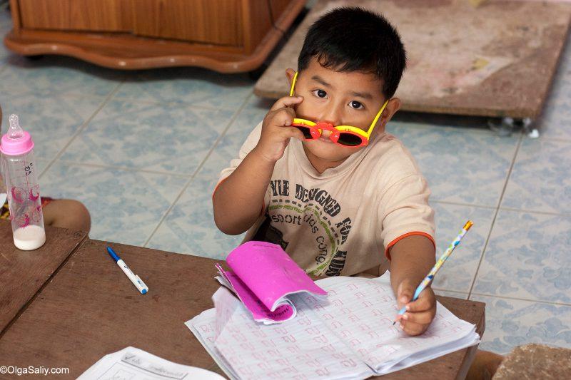 Тайский мальчик в очках пишет в прописи