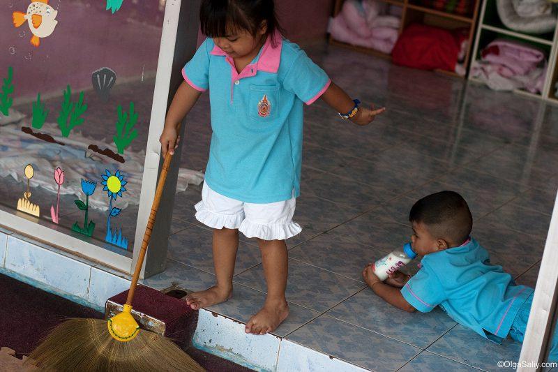 Девочка подметает пол в тайском детском саду