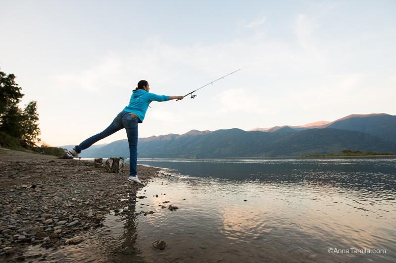 Девушка ловит рыбу в горном озере