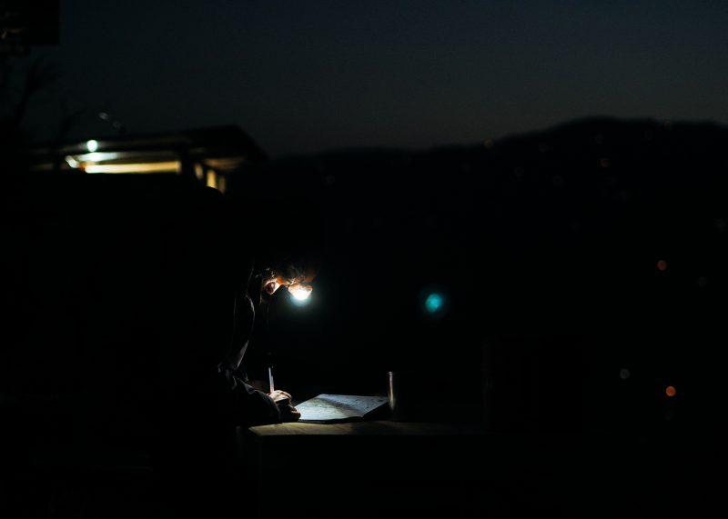 Волонтер пишет заметки вечером в комнате