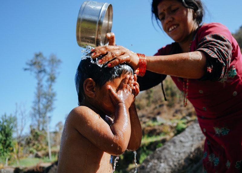 Женщина купает ребёнка. Непал