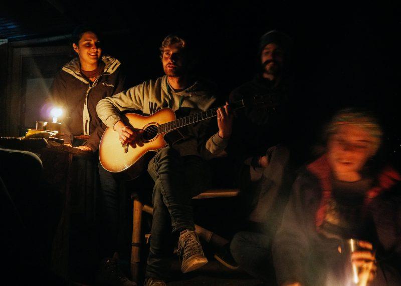 Ребята с гитарой при свете свечей