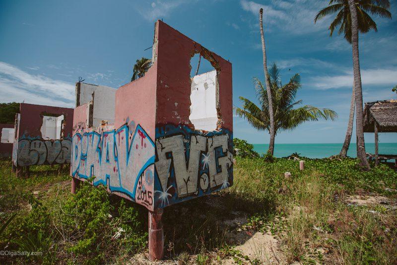 Заброшенный отель на берегу моря под пальмами