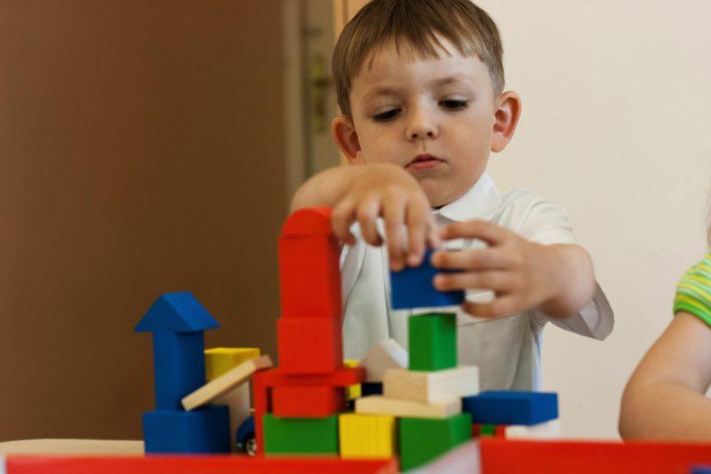 Мальчик играет в конструктор Лего