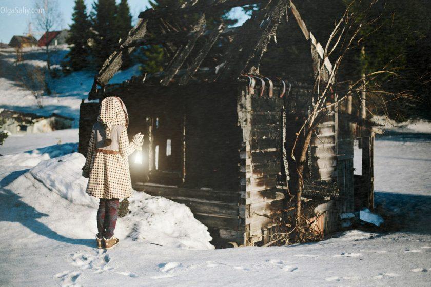 Девушка с фонариком возле сгоревшей избушки